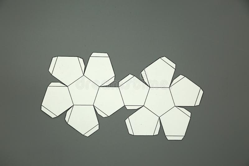 Γεωμετρική μορφή που αποκόπτει του εγγράφου και που φωτογραφίζεται στο γκρίζο υπόβαθρο dodecahedron 2$α μορφή πτυσσόμενη για να δ στοκ φωτογραφία