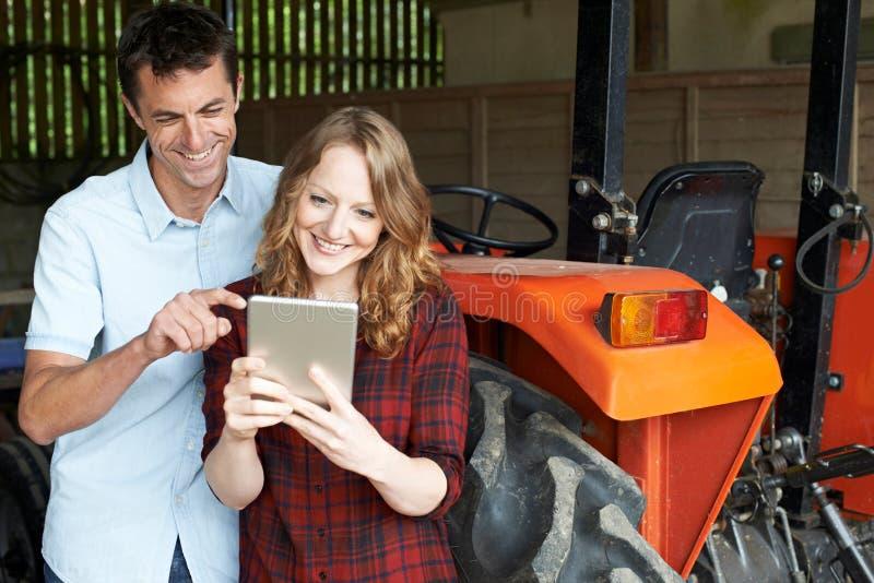 Γεωργικοί άνδρες και γυναίκες εργαζόμενοι που εξετάζουν την ψηφιακή ταμπλέτα στοκ φωτογραφία