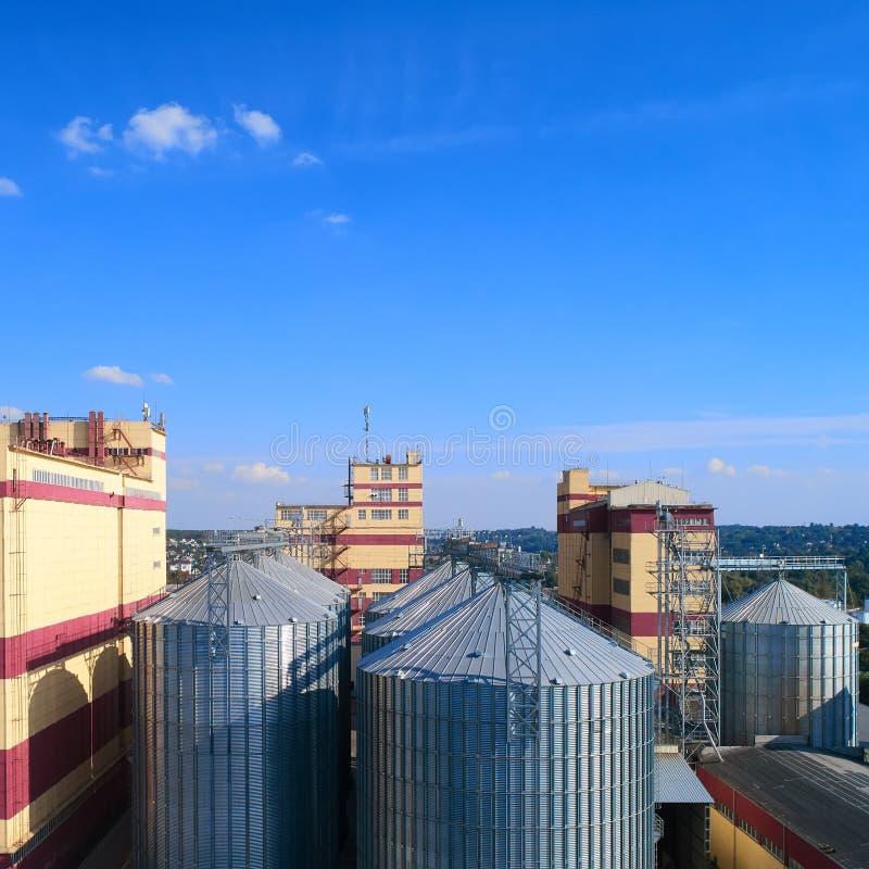 γεωργικό σιλό Αποθήκευση και ξήρανση των σιταριών, σίτος, καλαμπόκι, σόγια, ενάντια στο μπλε ουρανό με τα σύννεφα στοκ φωτογραφία