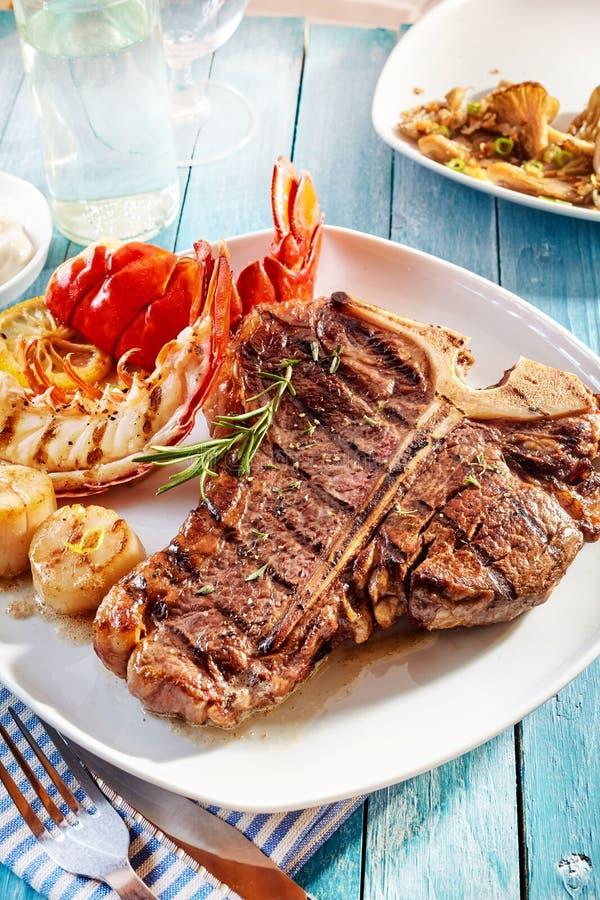 Γεύμα εύγευστης καλοψημένης κυματωγή και μπριζόλας και αστακών τύρφης στοκ εικόνα