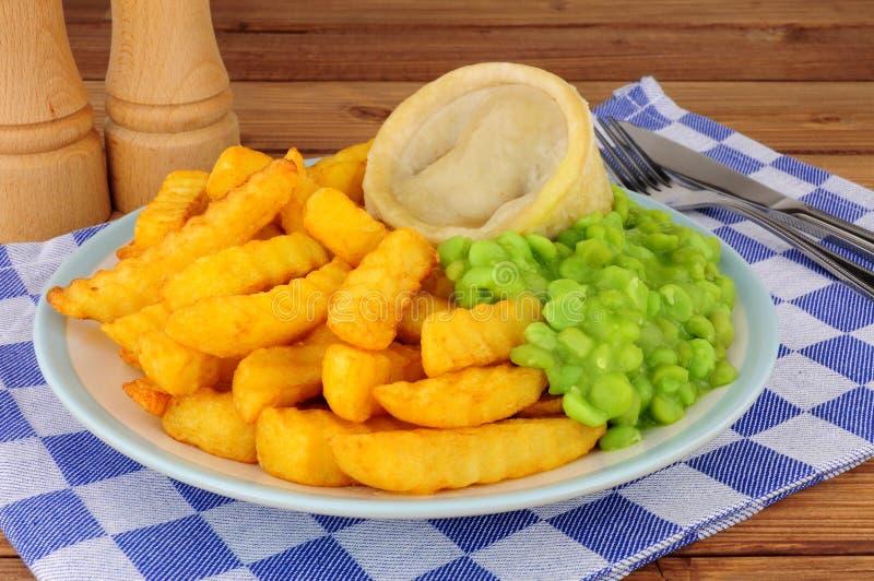 Γεύμα πουτίγκας μπριζόλας και νεφρών με τα τσιπ και τα Mushy μπιζέλια στοκ εικόνα