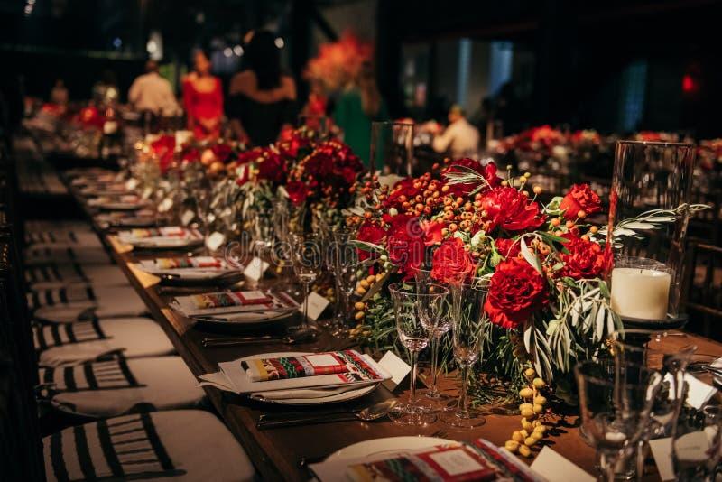 Γεύμα συμποσίου πολυτέλειας στο γεγονός που διακοσμείται με τα λουλούδια που περιμένουν τους φιλοξενουμένους στοκ φωτογραφία