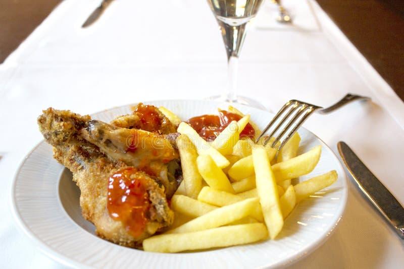 Γεύμα, τηγανιτές πατάτες με το κοτόπουλο στον πανικό στοκ εικόνες