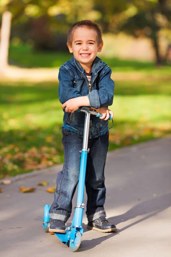 Γελώντας αγόρι με το μηχανικό δίκυκλο στοκ φωτογραφίες