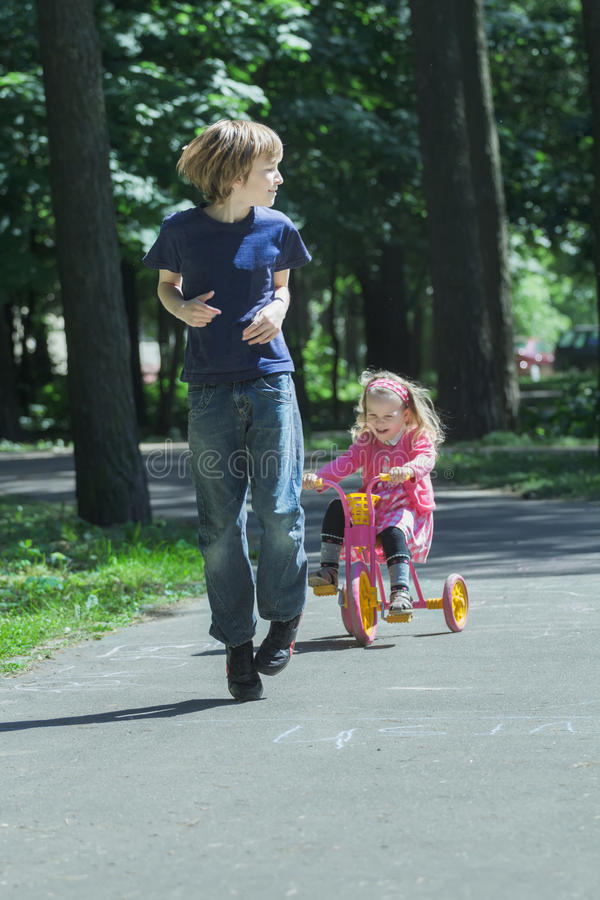 Γελώντας αδελφή αμφιθαλών που χαράζει μετά από τον αδελφό της στο ρόδινο και κίτρινο τρίκυκλο παιδιών στοκ φωτογραφίες