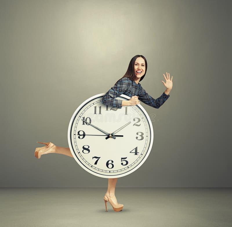 Γελώντας γυναίκα που κρατά το μεγάλο άσπρο ρολόι στοκ εικόνες