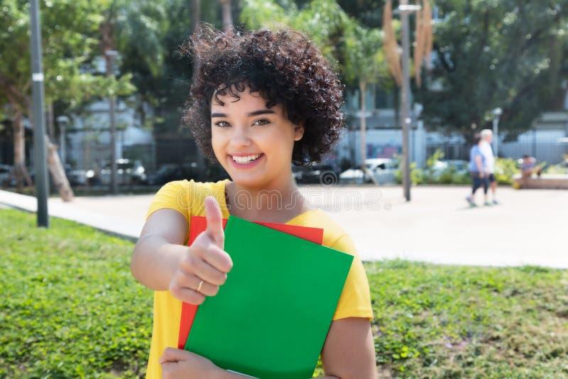 Γελώντας καυκάσια γυναίκα σπουδαστής με τη σγουρή τρίχα που παρουσιάζει αντίχειρα στοκ εικόνες με δικαίωμα ελεύθερης χρήσης