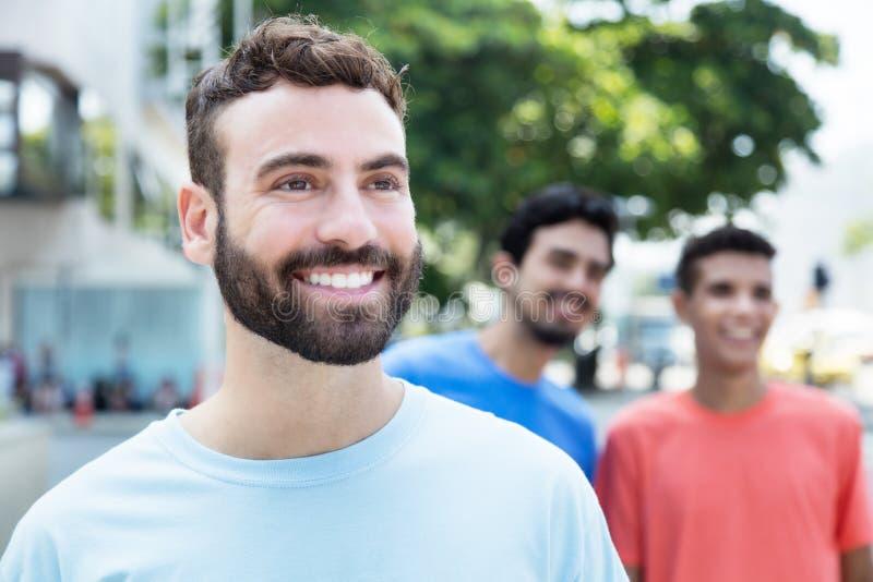 Γελώντας καυκάσιο άτομο με τη γενειάδα που περπατά με δύο φίλους στην πόλη στοκ εικόνα