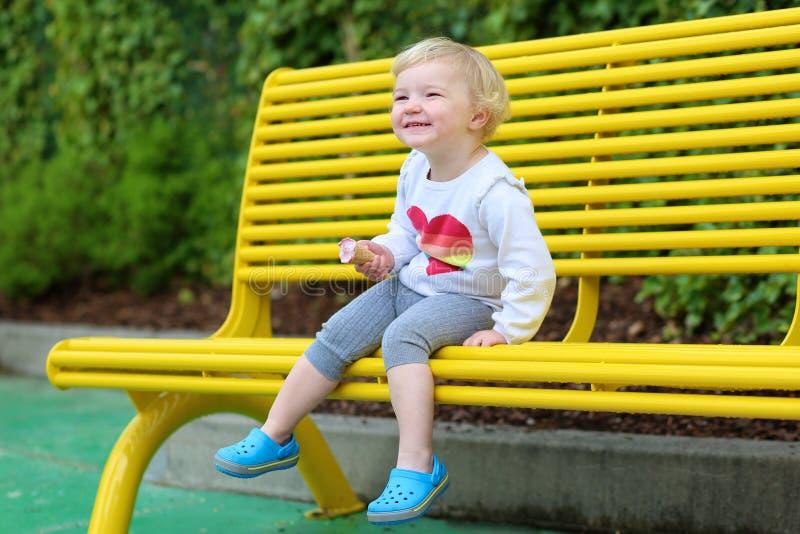 Γελώντας κορίτσι μικρών παιδιών που τρώει το παγωτό υπαίθρια στοκ εικόνες