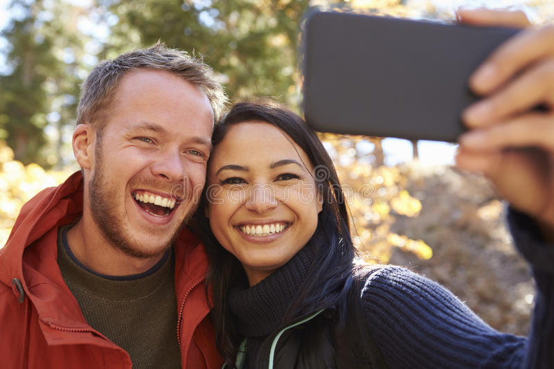 Γελώντας μικτό ζεύγος φυλών που παίρνει ένα selfie σε ένα δάσος στοκ φωτογραφίες με δικαίωμα ελεύθερης χρήσης