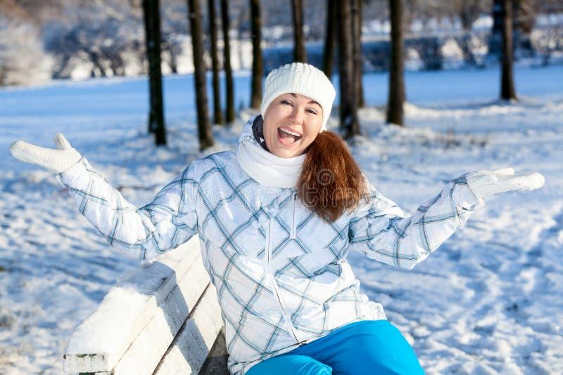 Γελώντας νέα γυναίκα στον πάγκο με τα χέρια επάνω, χειμερινό πάρκο στοκ φωτογραφία