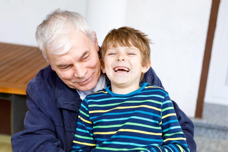 Γελώντας παππούς με τον εγγονό του καθώς παίζουν από κοινού στοκ εικόνες με δικαίωμα ελεύθερης χρήσης