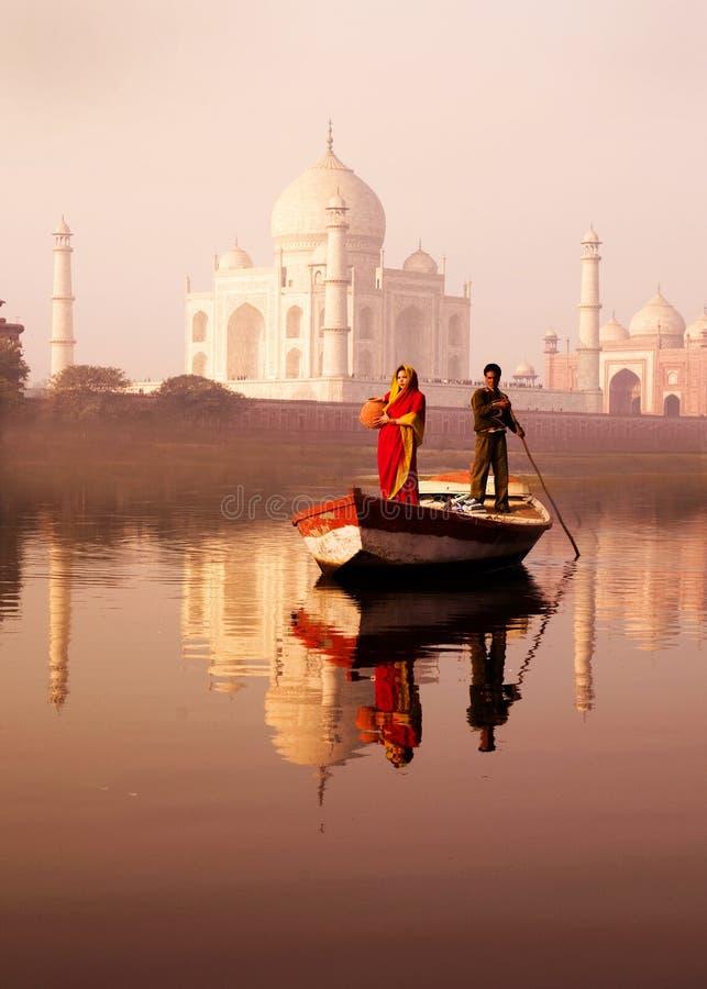Γηγενής ινδική άνδρας και γυναίκα στη βάρκα και ένα Taj Mahal στο Τ στοκ φωτογραφία