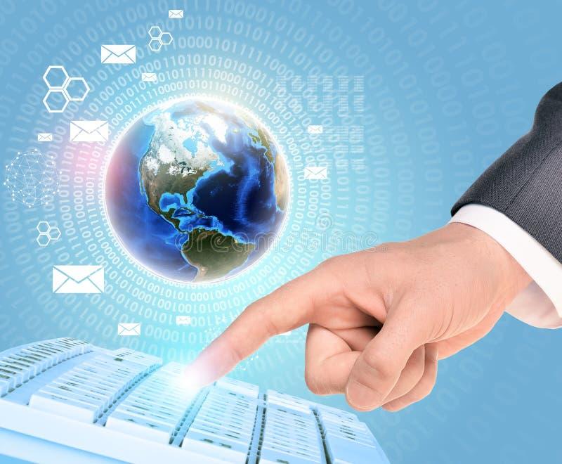 Γη και businessmans χέρι σχετικά με το πληκτρολόγιο στοκ φωτογραφία με δικαίωμα ελεύθερης χρήσης