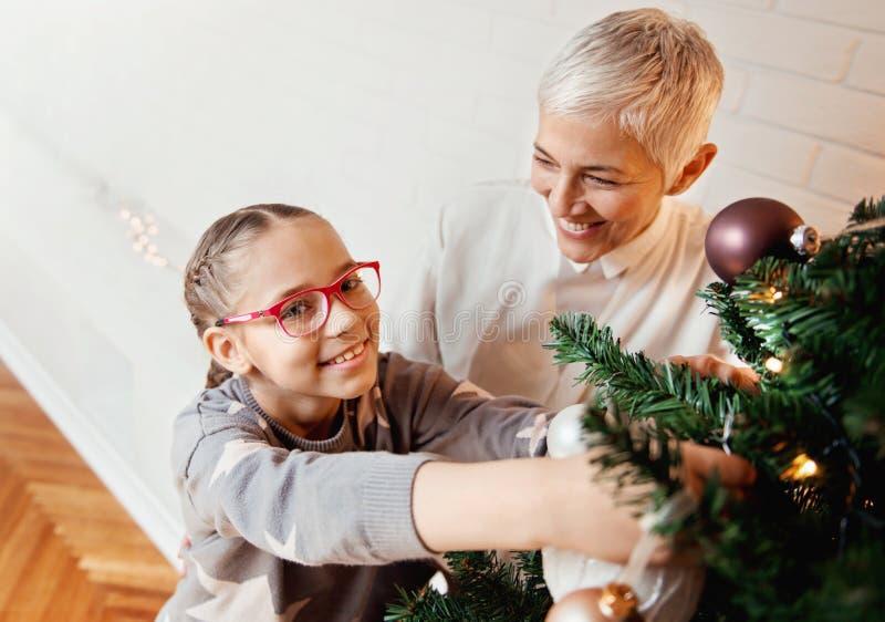 Γιαγιά και εγγονή που διακοσμούν ένα χριστουγεννιάτικο δέντρο στοκ εικόνες