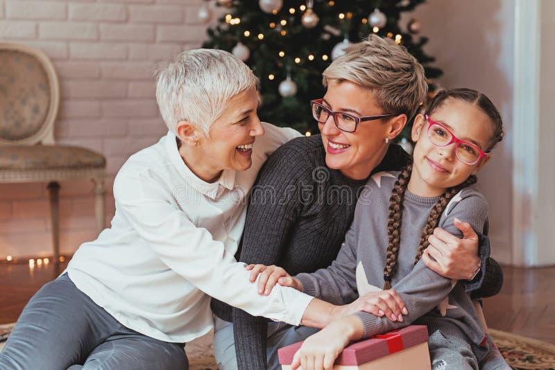 Γιαγιά και εγγονή που διακοσμούν Χριστούγεννα που μαζεύονται treeFamily γύρω από ένα χριστουγεννιάτικο δέντρο, θηλυκές γενεές στοκ εικόνες