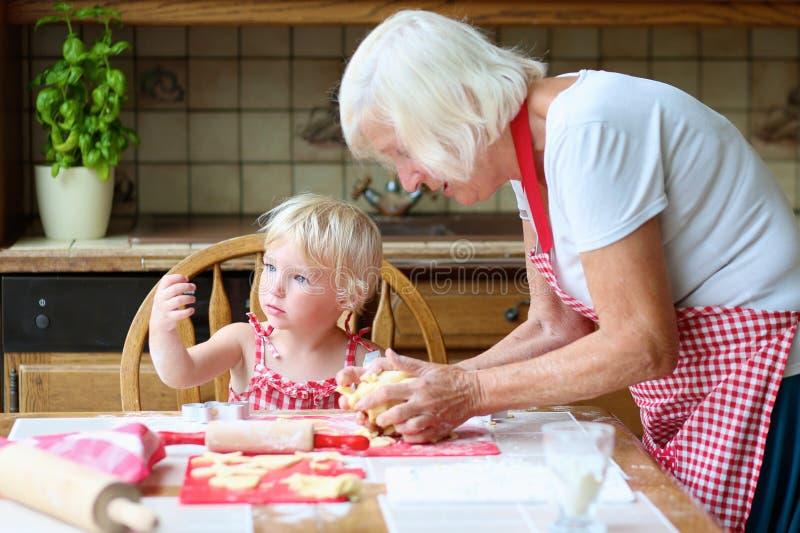 Γιαγιά και εγγονή που κατασκευάζουν τα μπισκότα από κοινού στοκ φωτογραφία με δικαίωμα ελεύθερης χρήσης