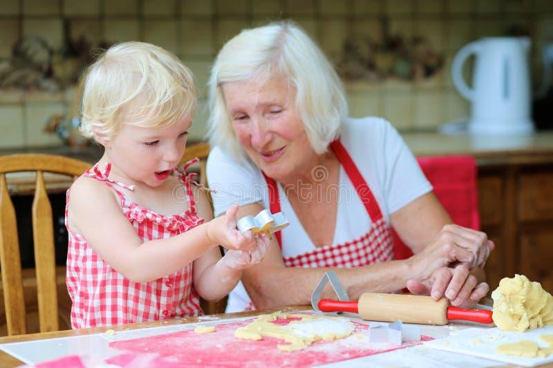 Γιαγιά και εγγονή που κατασκευάζουν τα μπισκότα από κοινού στοκ εικόνες με δικαίωμα ελεύθερης χρήσης