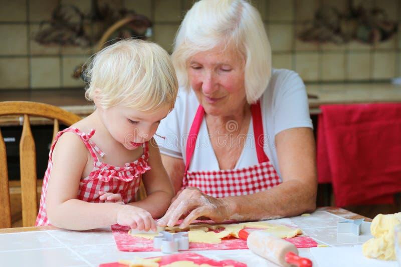 Γιαγιά και εγγονή που κατασκευάζουν τα μπισκότα από κοινού στοκ φωτογραφίες