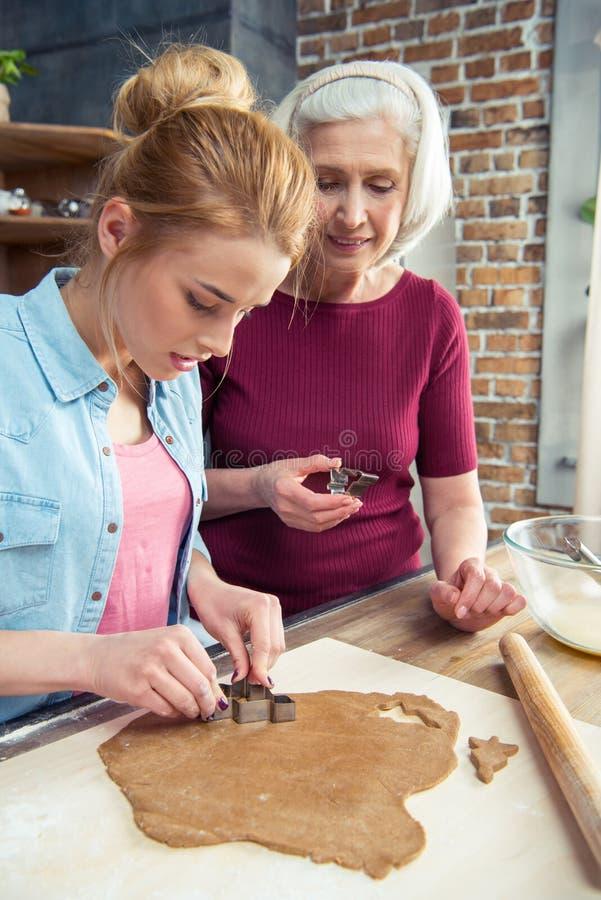 Γιαγιά και εγγονή που κατασκευάζουν τα μπισκότα στοκ εικόνες