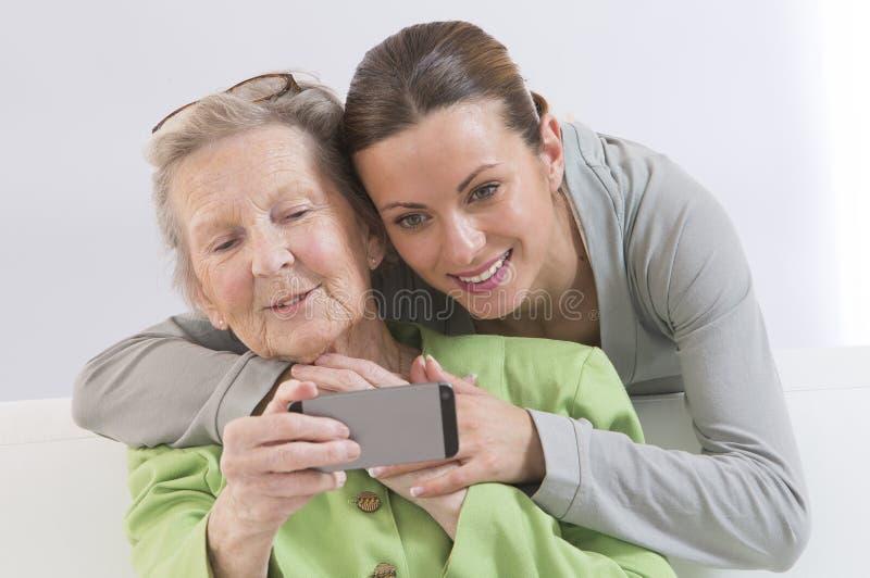Γιαγιά και ελκυστική νέα grand-daughter που φωτογραφίζουν το τ στοκ φωτογραφία με δικαίωμα ελεύθερης χρήσης