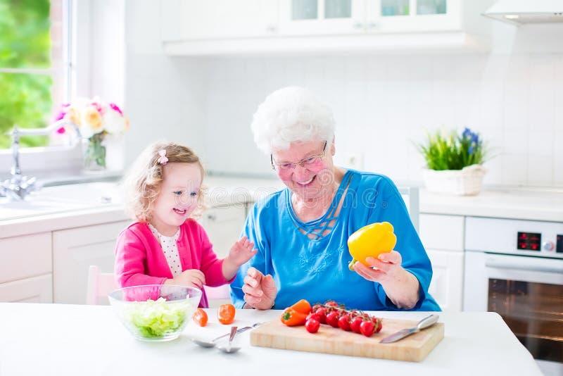 Γιαγιά και μικρό κορίτσι που κατασκευάζουν τη σαλάτα στοκ φωτογραφία με δικαίωμα ελεύθερης χρήσης