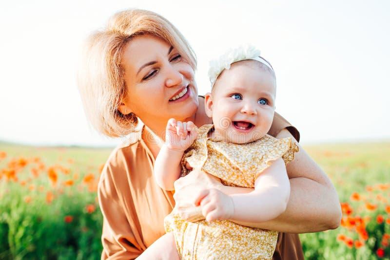 Γιαγιά με μια μικρή εγγονή που παίζει σε έναν τομέα παπαρουνών στοκ εικόνες