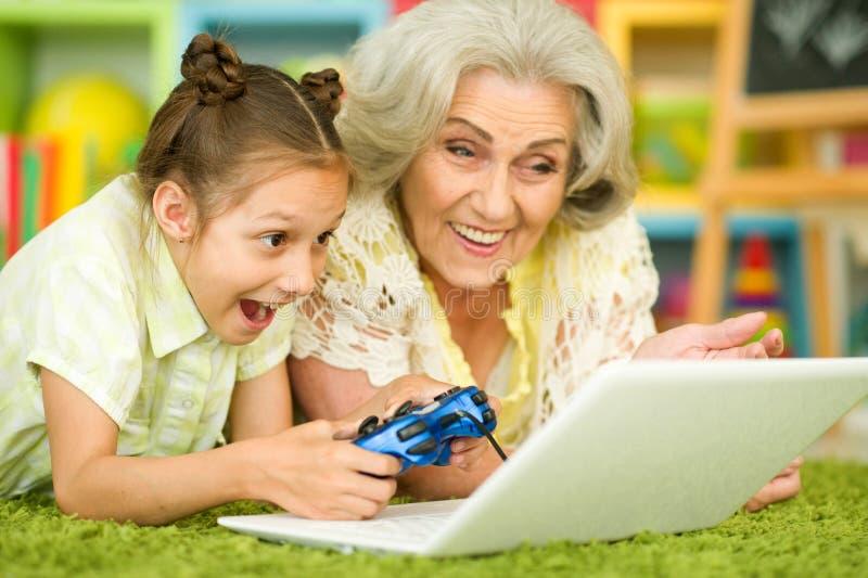 Γιαγιά με το παίζοντας παιχνίδι στον υπολογιστή εγγονών της στοκ φωτογραφίες