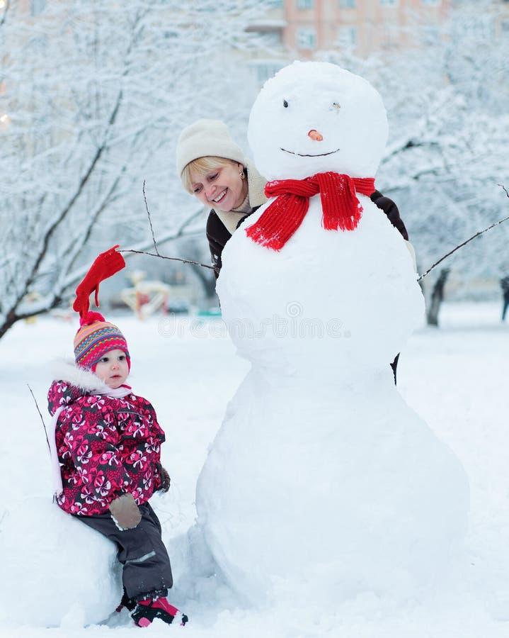 Γιαγιά με το παιχνίδι εγγονών στο χιόνι στοκ εικόνες