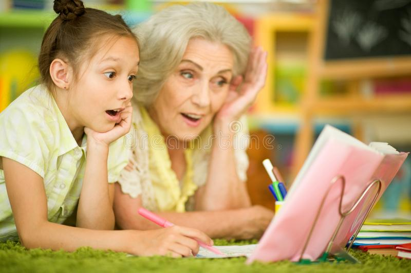 Γιαγιά με το χαριτωμένο μικρό κορίτσι που κάνει την εργασία από κοινού στοκ εικόνες με δικαίωμα ελεύθερης χρήσης