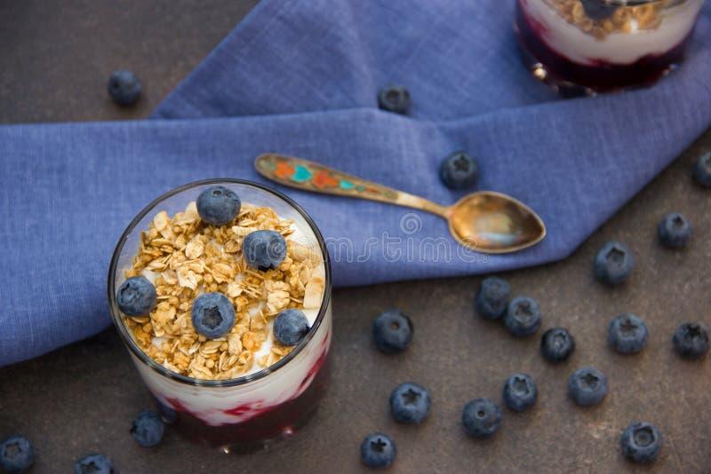 Γιαούρτι με το granola και τα φρέσκα βακκίνια, στο κύπελλο γυαλιού πέρα από το παλαιό υπόβαθρο στοκ εικόνες