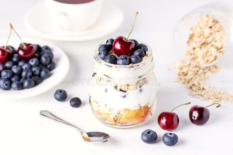 Γιαούρτι με Oatmeal τα φρούτα και υγιή ανωτέρω υποβάθρου προγευμάτων διατροφής μούρων αγροτικό άσπρο ξύλινο οριζόντιο στοκ φωτογραφίες