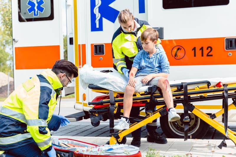 Γιατροί έκτακτης ανάγκης που φροντίζουν για το αγόρι θυμάτων ατυχήματος στοκ φωτογραφία με δικαίωμα ελεύθερης χρήσης