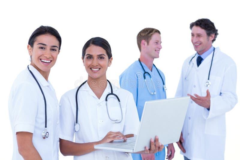 Γιατροί και νοσοκόμες που συζητούν και που χρησιμοποιούν το lap-top στοκ εικόνες
