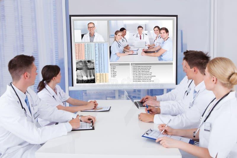 Γιατροί που διοργανώνουν τη συνεδρίαση της τηλεδιάσκεψης στο νοσοκομείο στοκ φωτογραφία