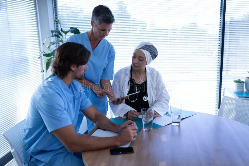 Γιατροί που συζητούν πέρα από την ψηφιακή ταμπλέτα στην κλινική στο νοσοκομείο στοκ φωτογραφία με δικαίωμα ελεύθερης χρήσης