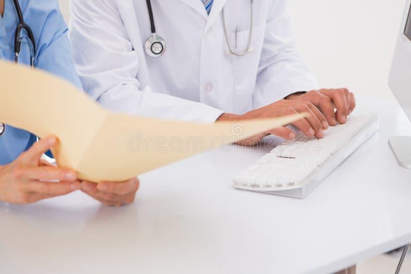 Γιατροί που χρησιμοποιούν τον υπολογιστή που εξετάζει τα αρχεία στοκ εικόνα