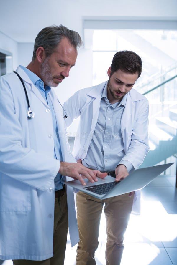 Γιατροί που χρησιμοποιούν το lap-top στο διάδρομο στοκ εικόνα