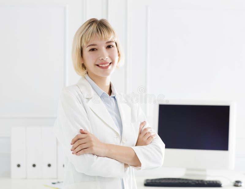 Γιατρός γυναικών με το άσπρο παλτό που στέκεται στο νοσοκομείο στοκ φωτογραφία