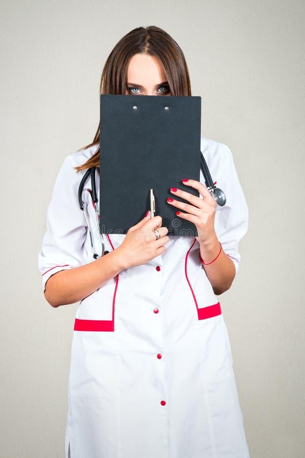 Γιατρός γυναικών, νοσοκόμα που κρατά έναν φάκελλο και τις καλύψεις το πρόσωπό της, το ey της στοκ φωτογραφία με δικαίωμα ελεύθερης χρήσης