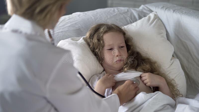 Γιατρός γυναικών που εξετάζει προσεκτικά το άρρωστο παιδί με το στηθοσκόπιο, να φωνάξει μικρών κοριτσιών στοκ εικόνα