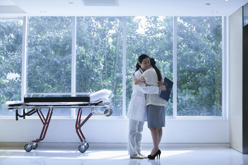 Γιατρός και ασθενής που αγκαλιάζουν σε ένα νοσοκομείο δίπλα σε ένα φορείο, πλήρες μήκος στοκ εικόνες