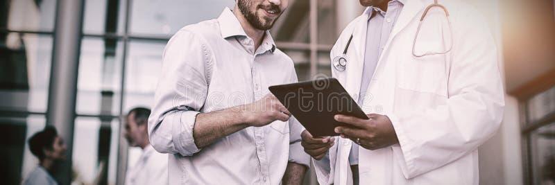 Γιατρός και ασθενής που διοργανώνουν τη συζήτηση σχετικά με την ψηφιακή ταμπλέτα στοκ φωτογραφία