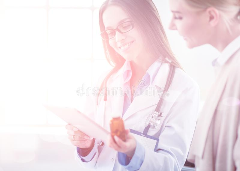 Γιατρός και ασθενής που συζητούν κάτι καθμένος στον πίνακα o στοκ φωτογραφία με δικαίωμα ελεύθερης χρήσης