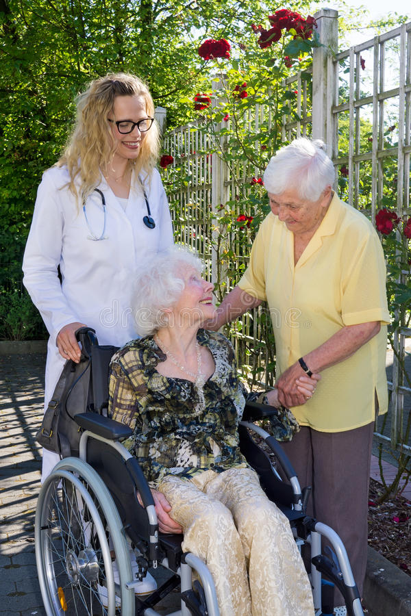 Γιατρός και βοηθητικοί φροντίζοντας ηλικιωμένοι στον κήπο στοκ εικόνα με δικαίωμα ελεύθερης χρήσης