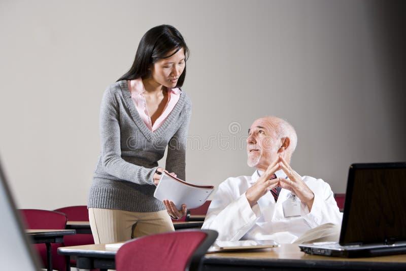 Γιατρός και γυναίκες βοηθός στη αίθουσα συνδιαλέξεων στοκ εικόνα