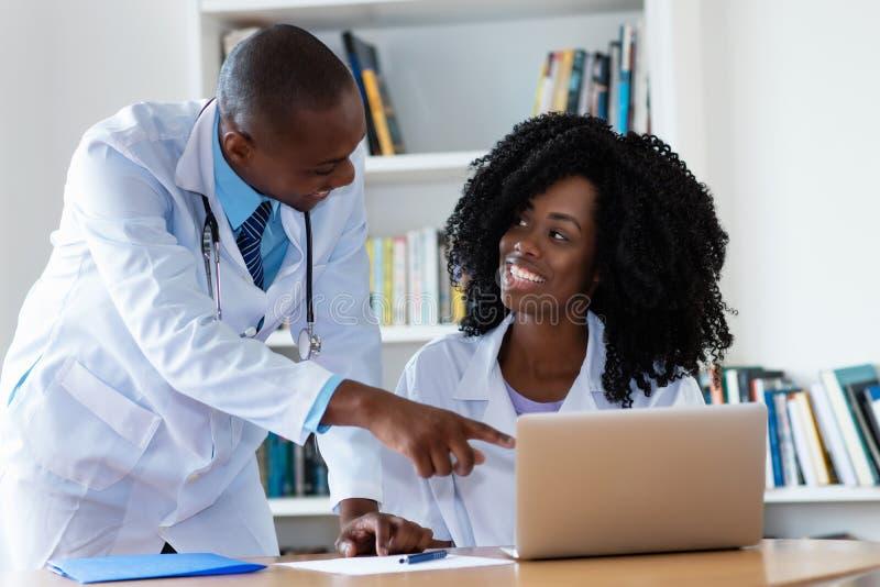 Γιατρός και νοσοκόμα αρσενικών αφροαμερικάνων που εργάζονται στον υπολογιστή στοκ εικόνες