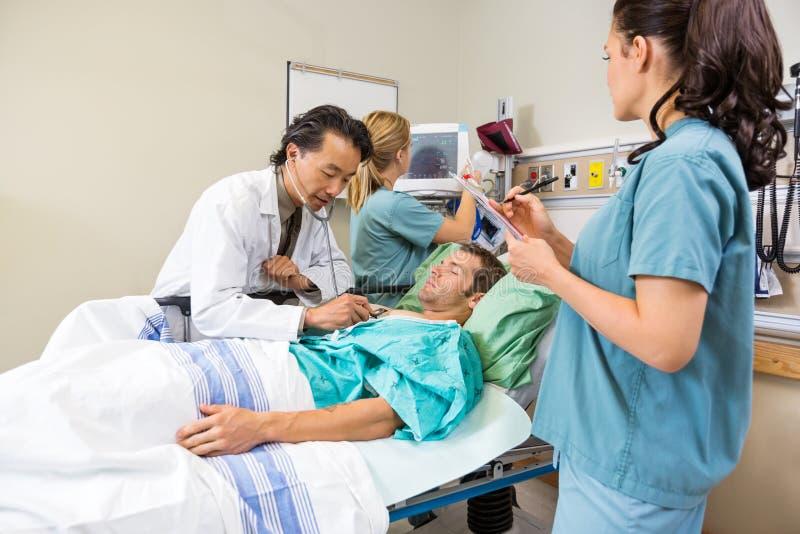 Γιατρός και νοσοκόμες που εξετάζουν τον ασθενή στο νοσοκομείο στοκ εικόνες