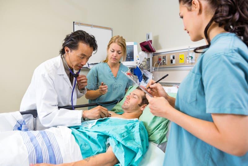 Γιατρός και νοσοκόμες που εξετάζουν τον ασθενή στοκ φωτογραφία με δικαίωμα ελεύθερης χρήσης