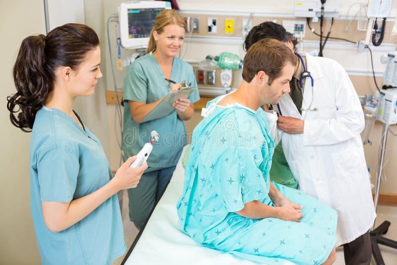 Γιατρός και νοσοκόμες που εξετάζουν τον ασθενή στοκ εικόνα
